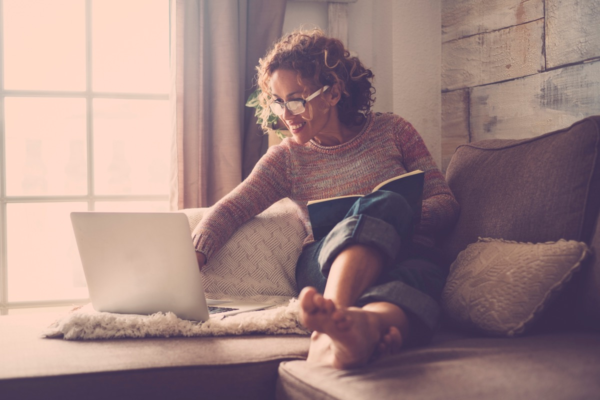 middle age woman working at home sit on the sofa using a laptop