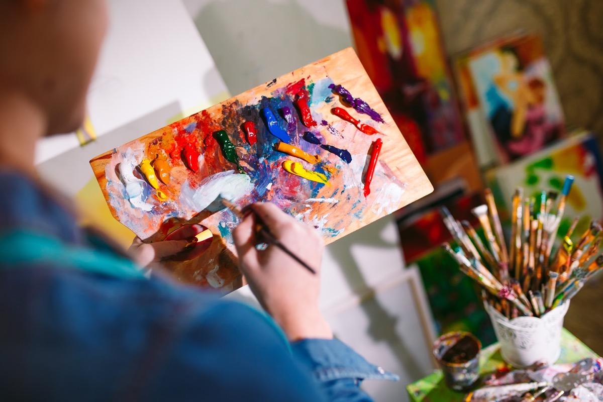 hand paints canvas