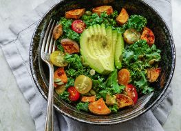Bowl of paleo diet foods with kale, avocado, tomatoes, and potatoes
