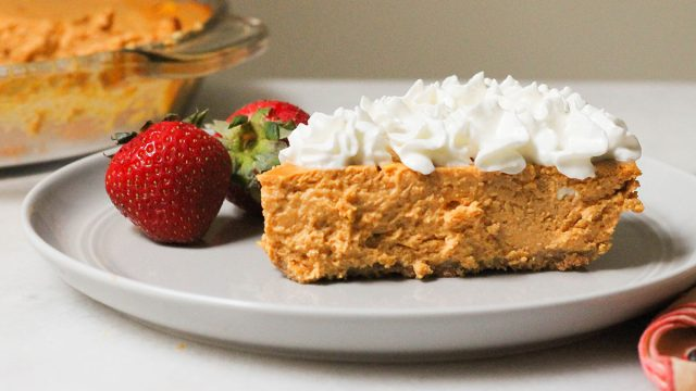 Slice of healthy pumpkin cheesecake with whipped cream and strawberries