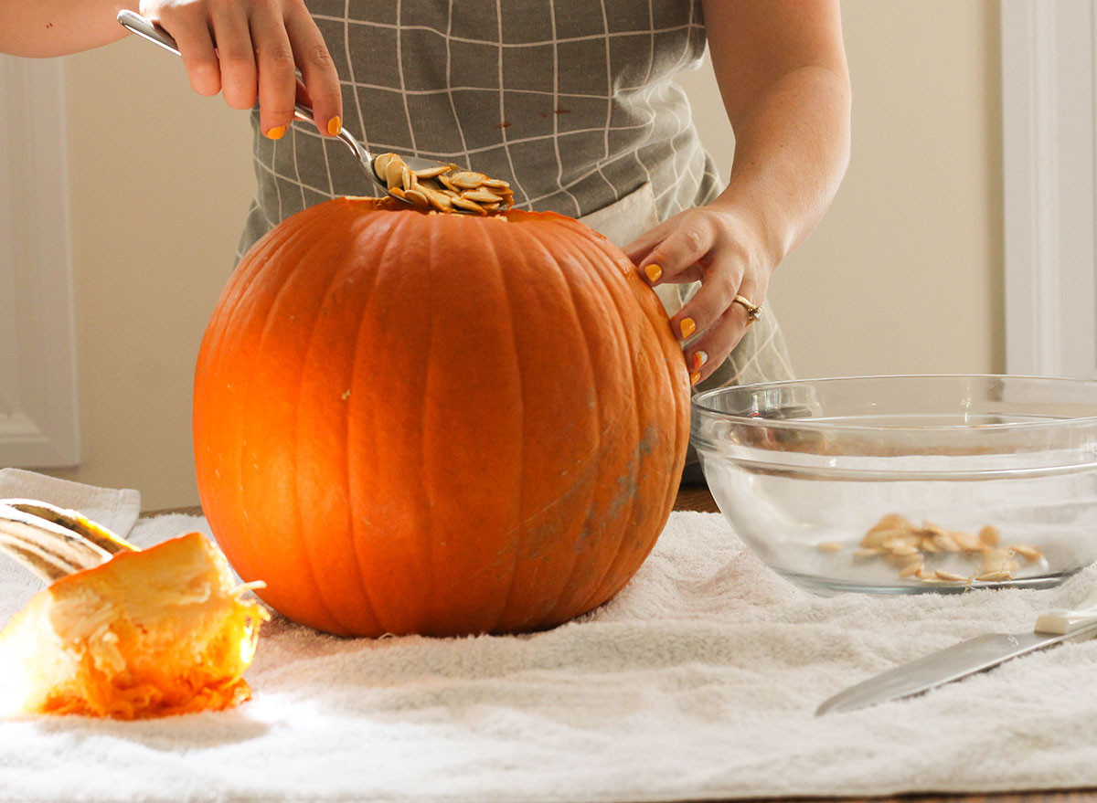Scooping out pumpkin seeds into a bowl from a pumpkin