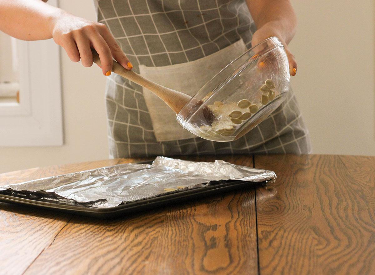 Spreading pumpkin seeds onto a baking sheet with aluminum foil