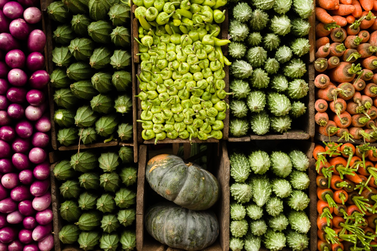 Several varieties of tropical vegetables neatly arranged for sale