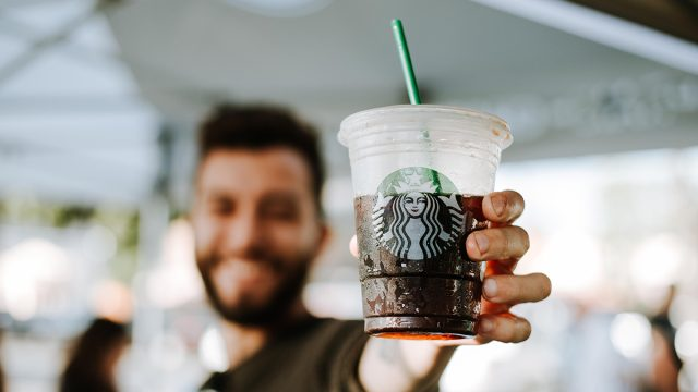 Starbucks customer holding an iced coffee in the summer time