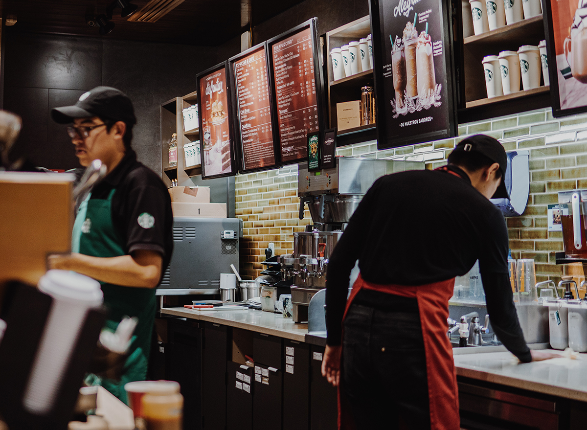 Starbucks employees serving customers behind the counter