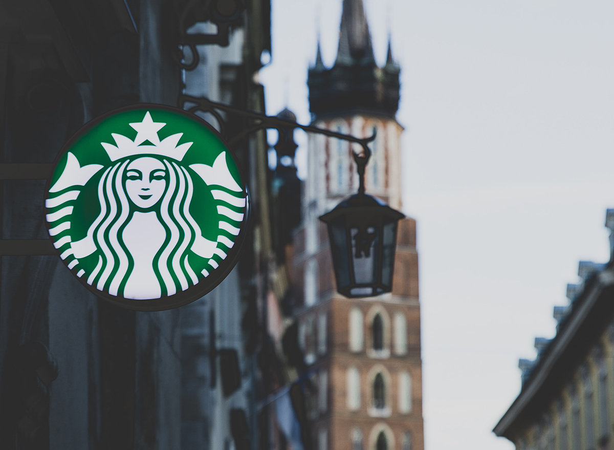 Starbucks sign glowing in a city