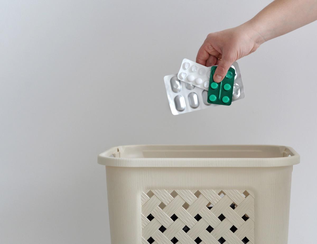 hand throwing pills away