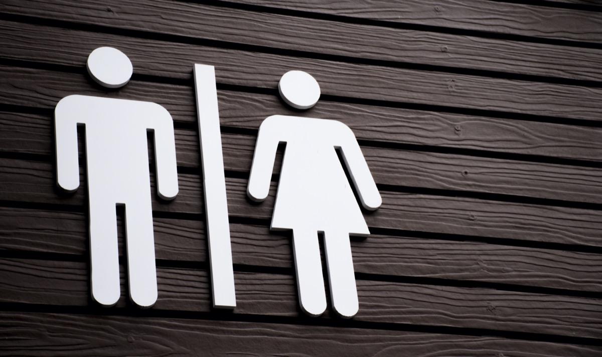 Restroom sign on a toilet door,on wood background