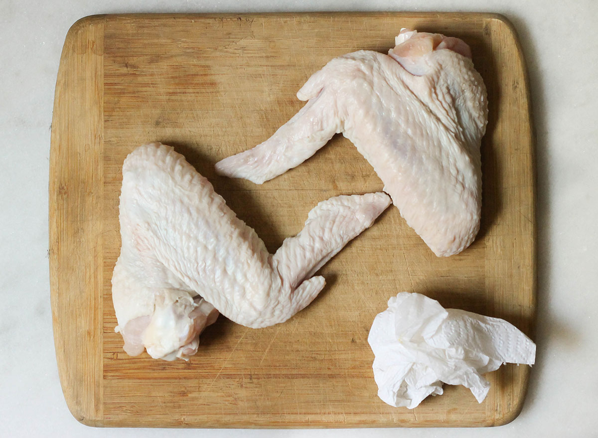Patting down turkey wings with a paper towel