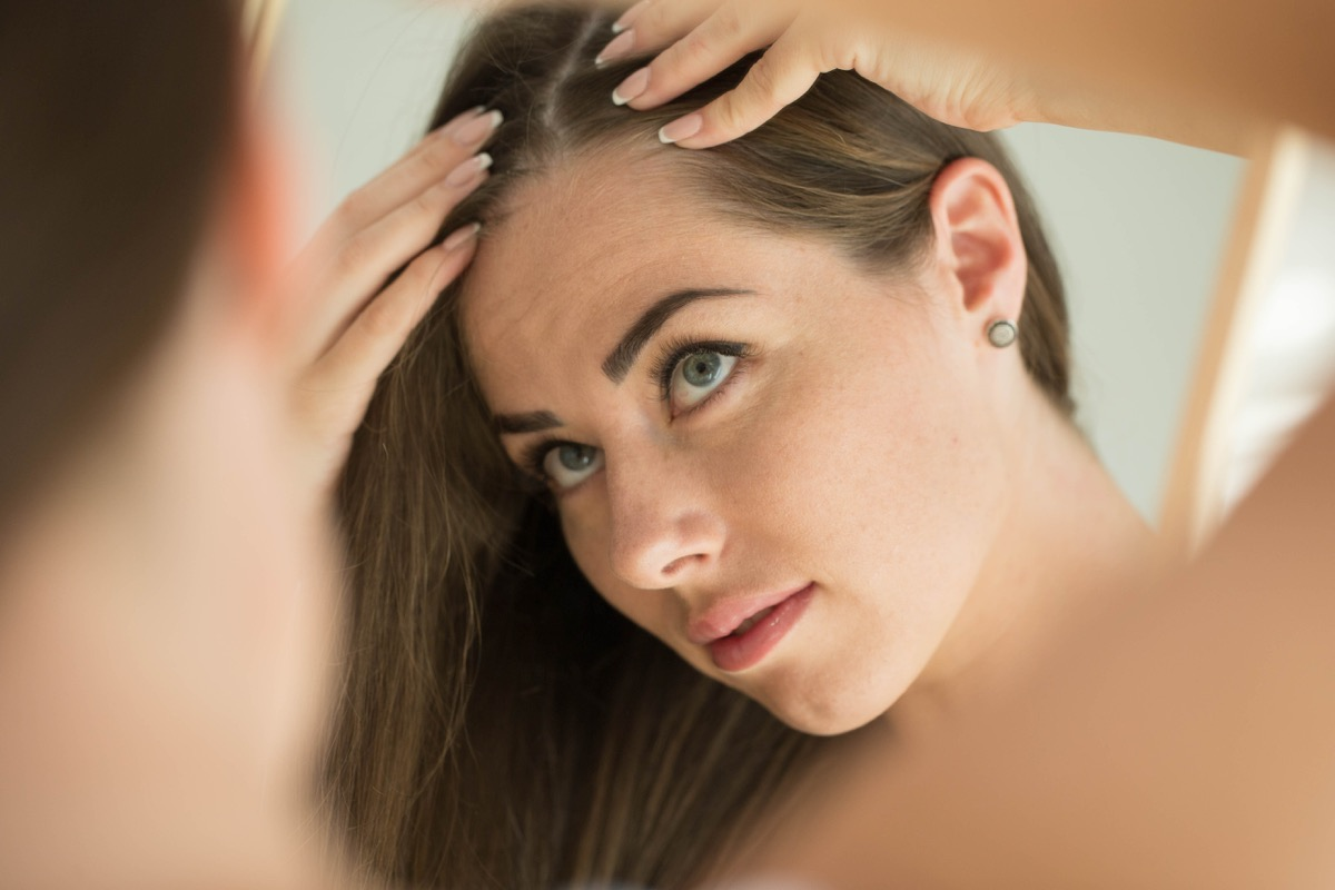 Woman touches her hair in front of the mirror