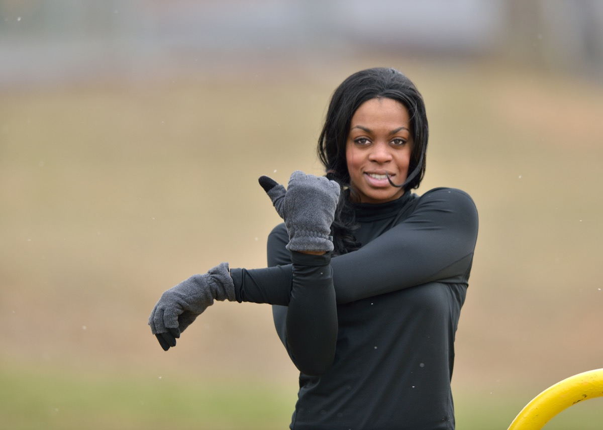 Woman in black fitness gear stretching in a park - cold weather