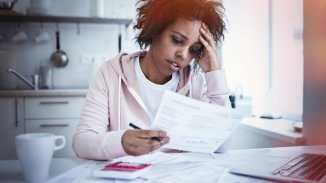 female sitting at kitchen table with laptop, dealing with financial stress