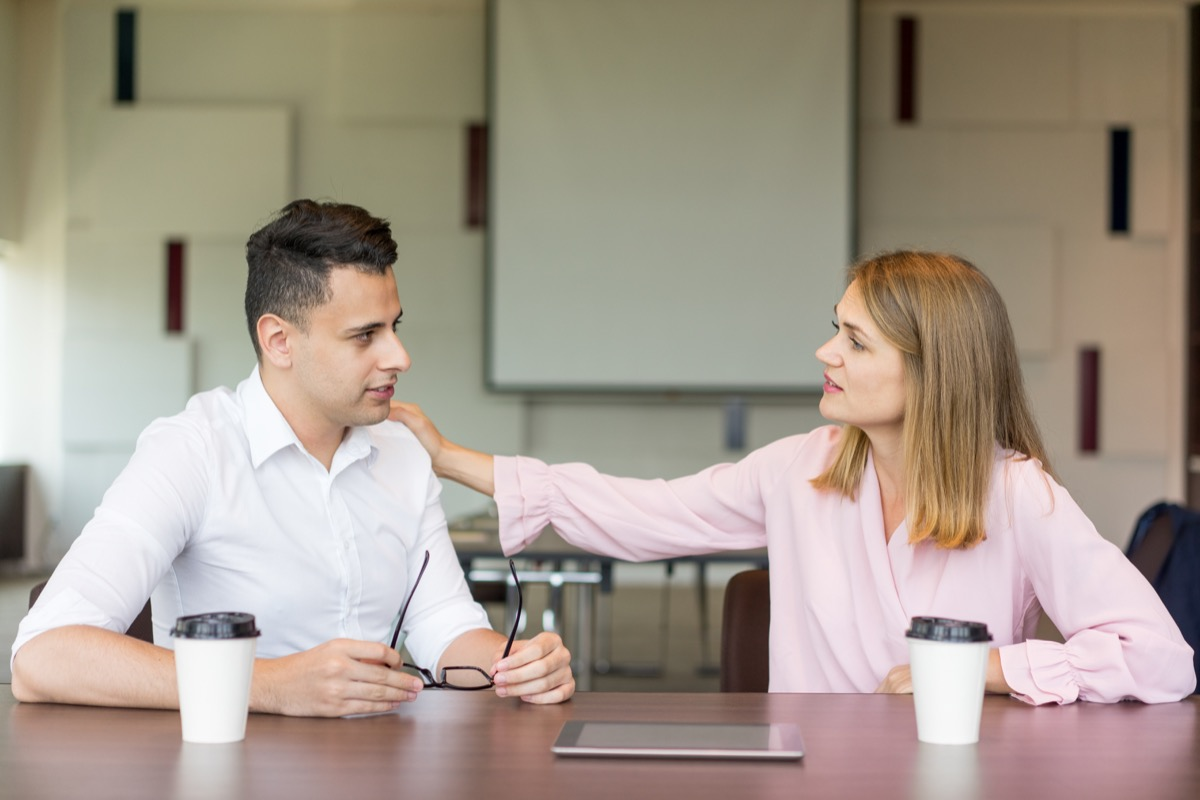 woman tapping male colleague on shoulder at coffee break.