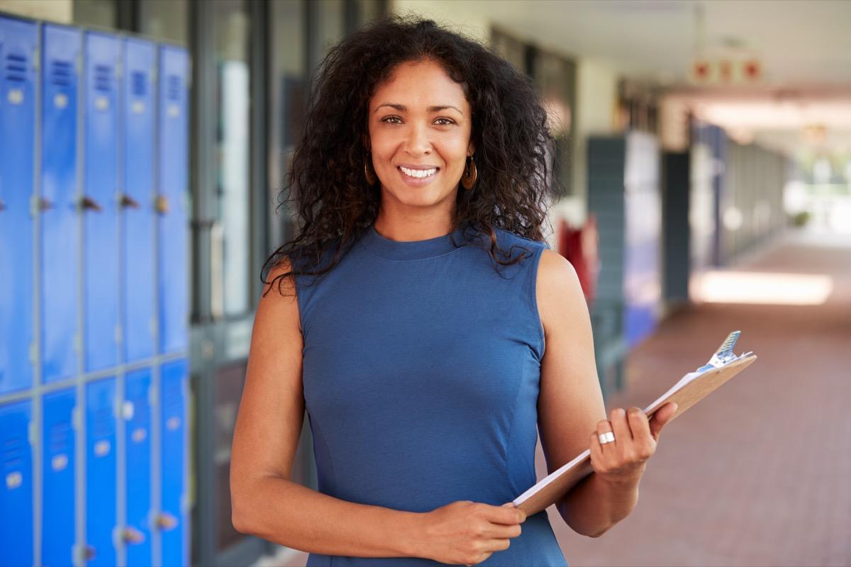 teacher smiling in school corridor
