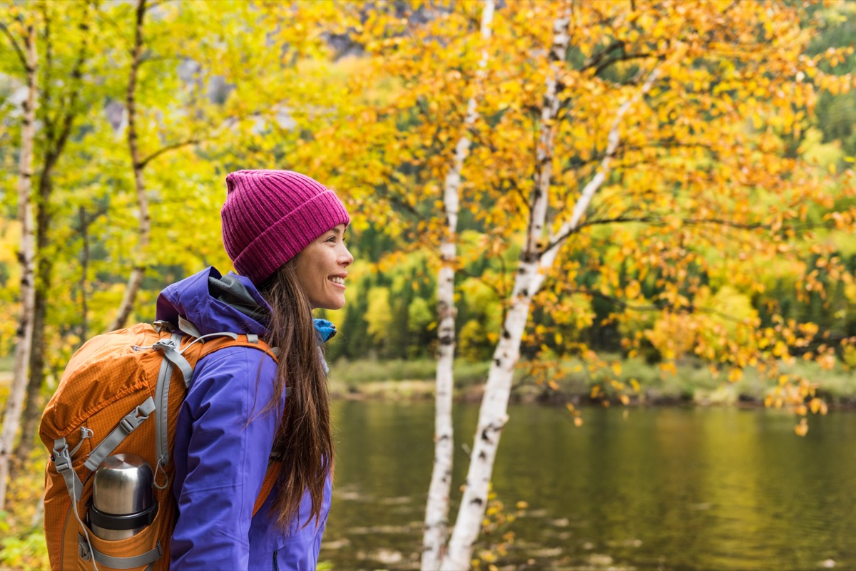 Woman hiker hiking looking at scenic view of fall foliage mountain landscape
