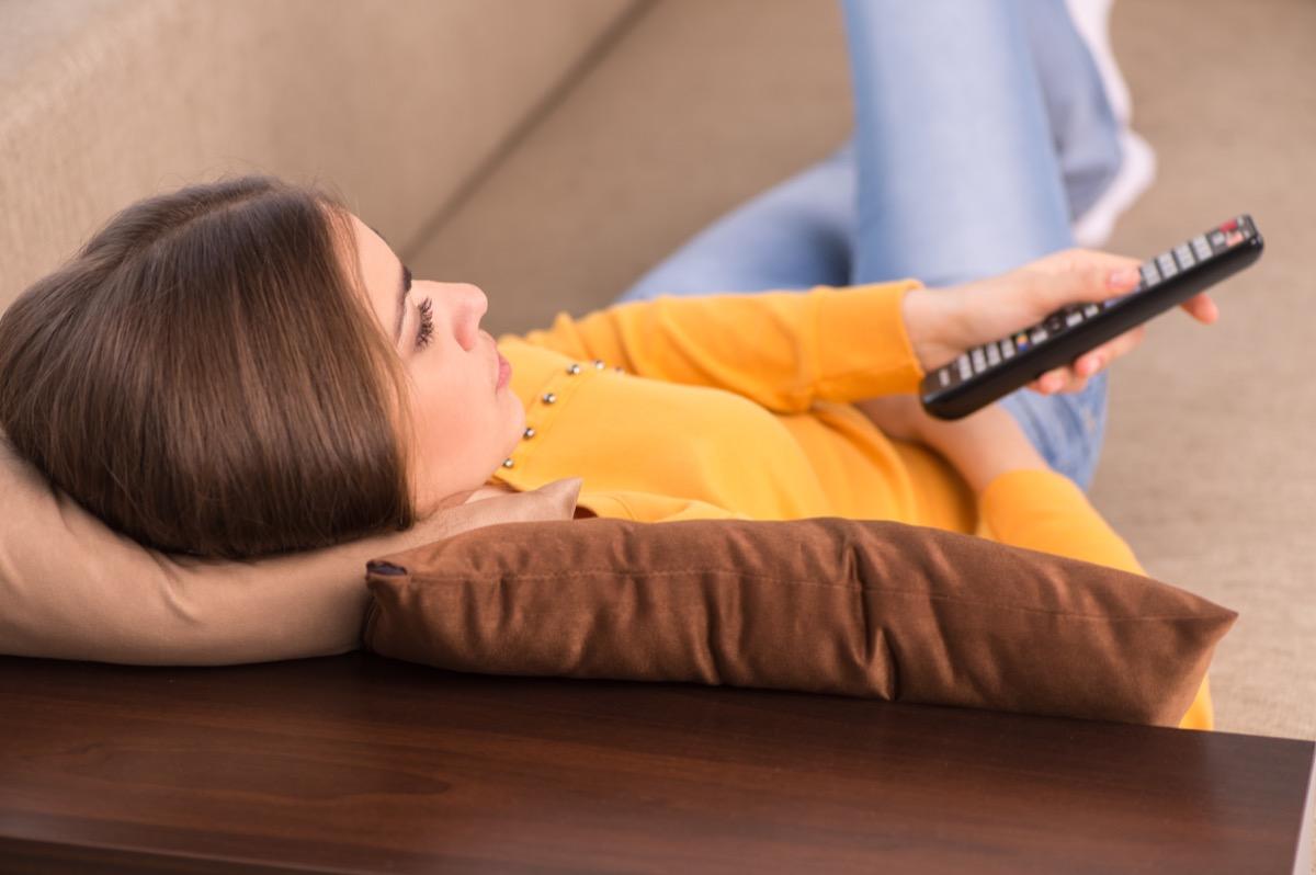 woman lying on sofa and watching tv.