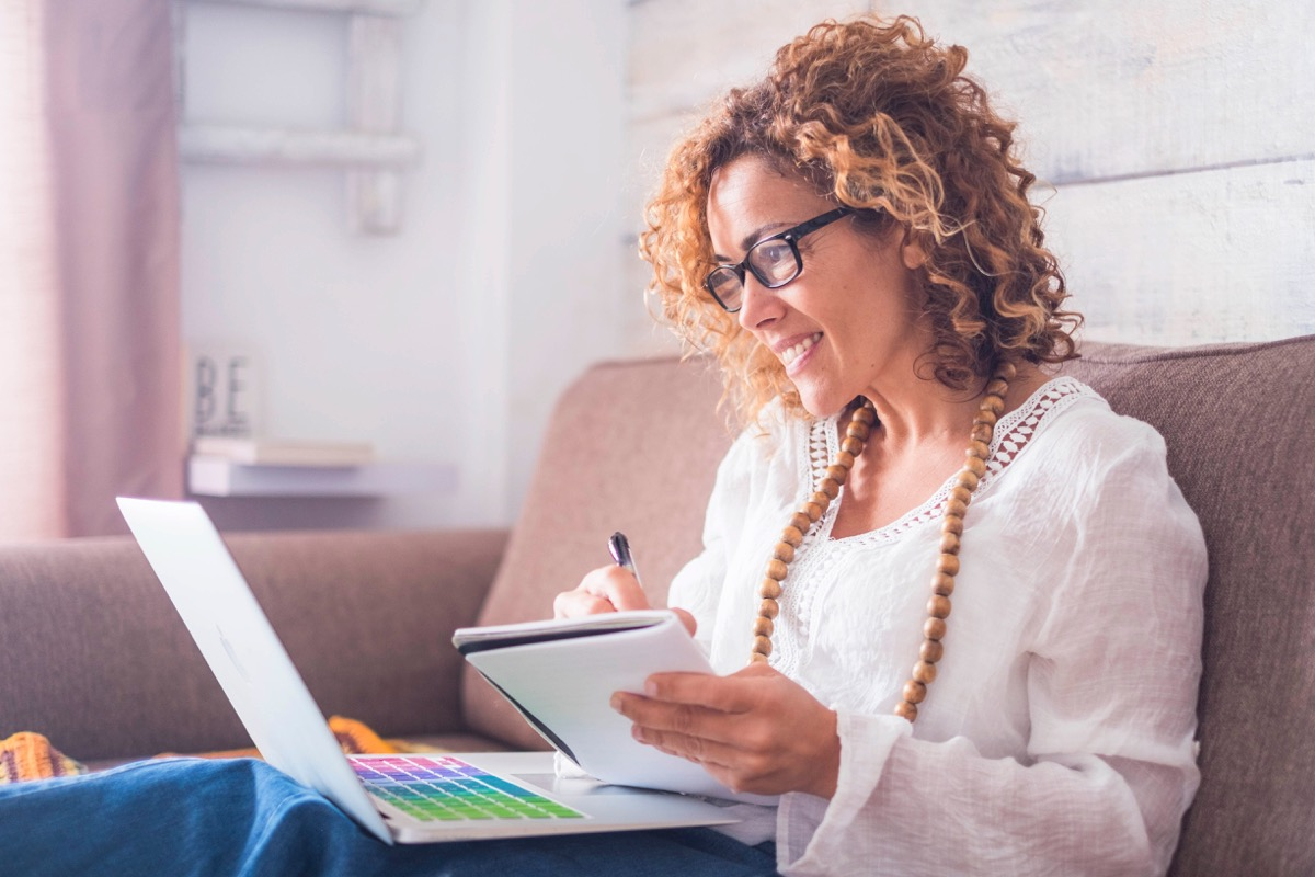 middle age woman working at home with laptop and notebook. writing a note