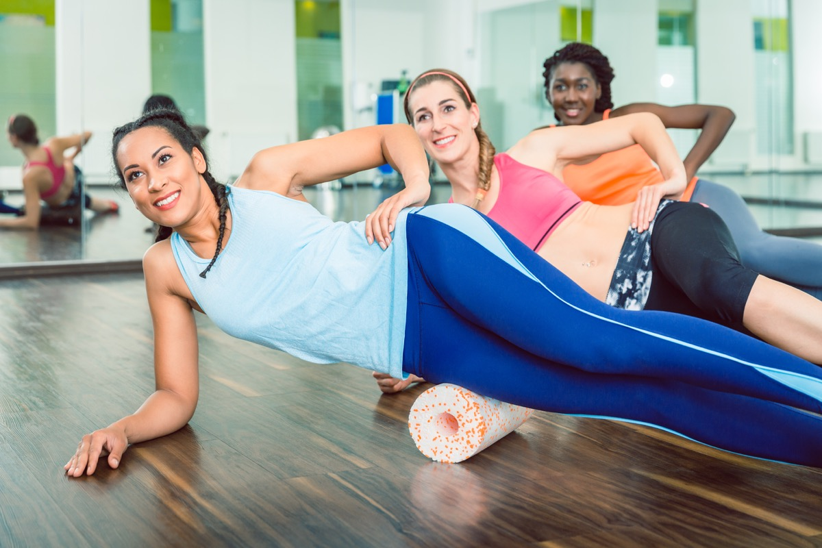 woman smiling while wearing blue fitness sleeveless top and leggings during group workout class of foam rolling at the gym