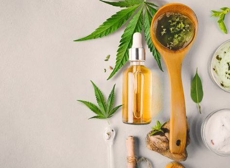 CBD oils in wooden spoon and glass bottle