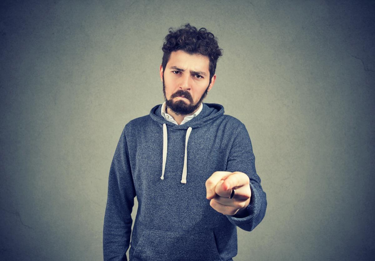 sad man with beard pointing at camera indicating guilt and blaming in anger