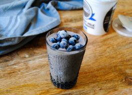 paleo blueberry meal replacement shake with blueberries on top in glass