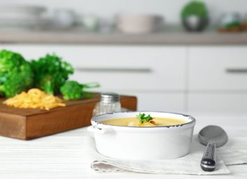 broccoli cheese soup in a bowl with sides of extra broccoli and cheese in the kitchen