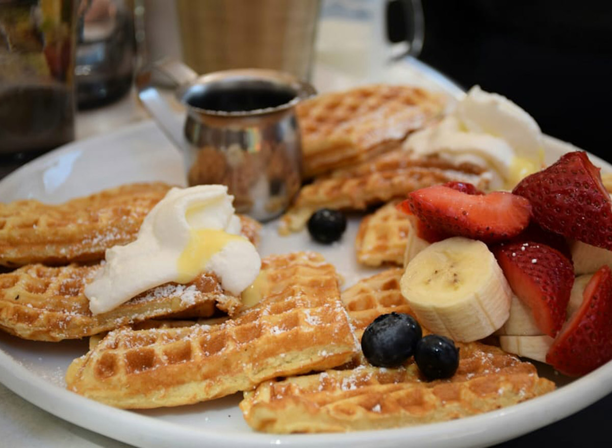 waffles with fruit and whipped cream with syrup on the side from cafe la maude