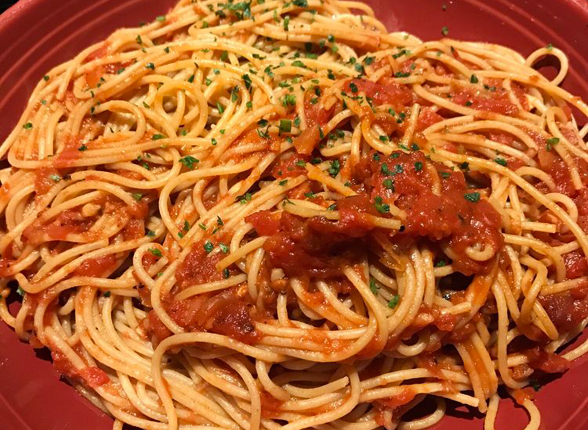 carrabbas whole grain spaghetti with pomodoro sauce on red plate