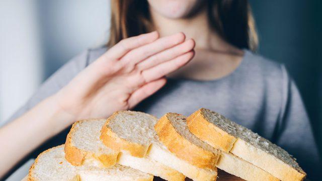 Woman refusing bread because of her celiac disease diet