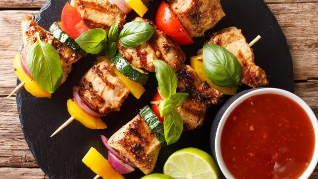 Chicken skewers on a round plate with salsa and limes