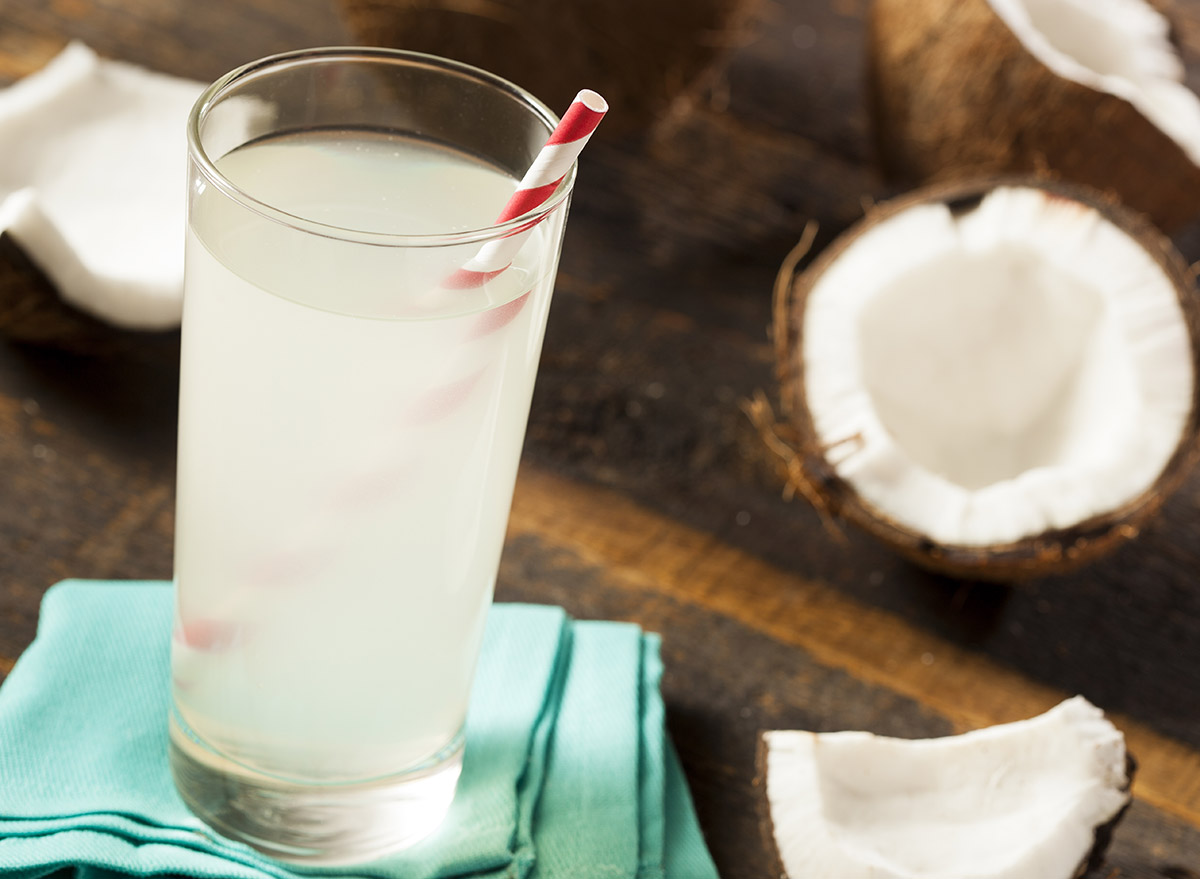 coconut water in a glass surrounded by slices coconuts