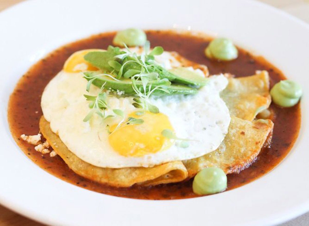 toastada dish with an egg on top in a red sauce from con huevos