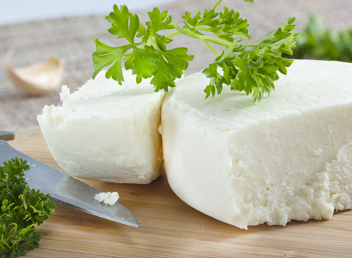 cotija cheese with cilantro cut up on a cutting board