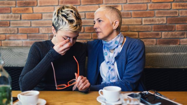 Sad and unhappy daughter sitting in cafe bar or restaurant with her mother and talking
