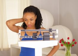 woman disappointed after checking weight