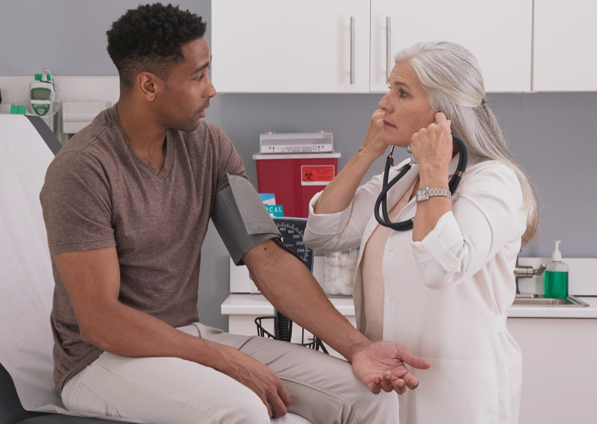 female physician checking male patients blood pressure at clinic