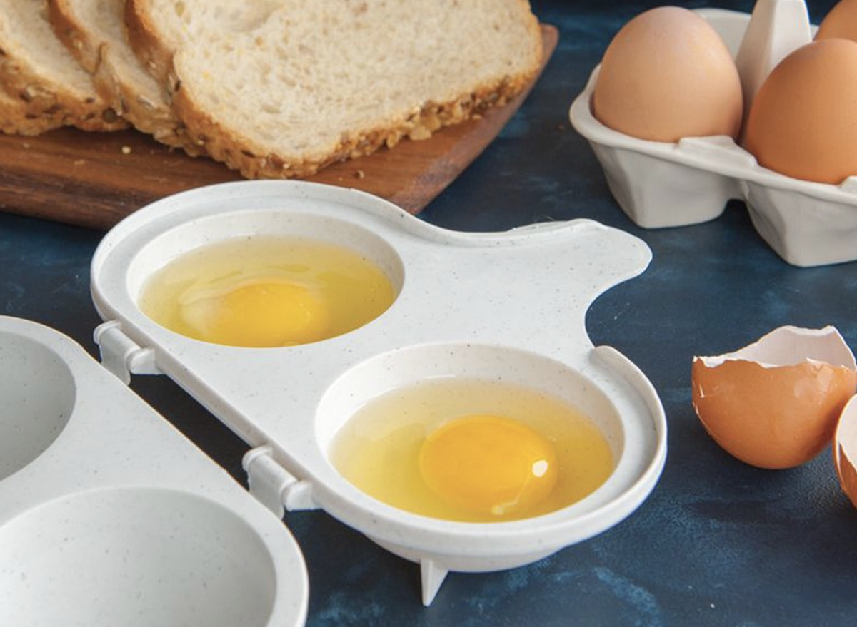 two eggs in a white container next to sliced bread