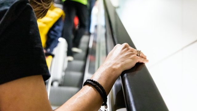 Person holding onto handrail of escalator in public