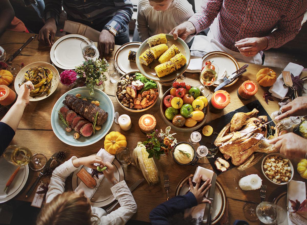 family celebrating thanksgiving at the table eating dinner