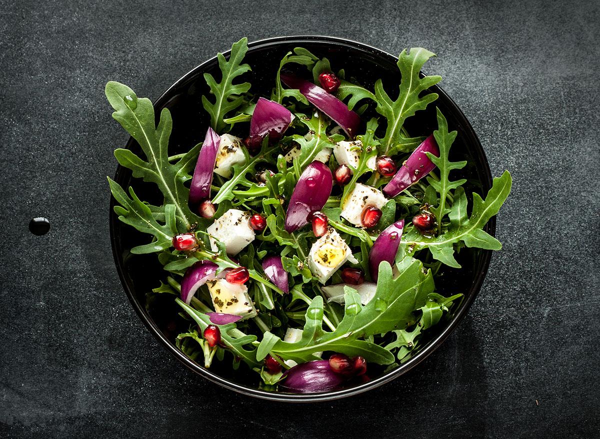 fresh arugula salad with feta, onion, and pomegranate