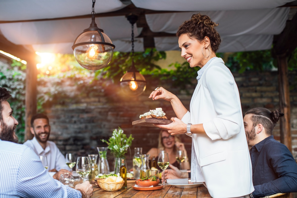 woman putting a plate with meal on dining table at backyard celebration