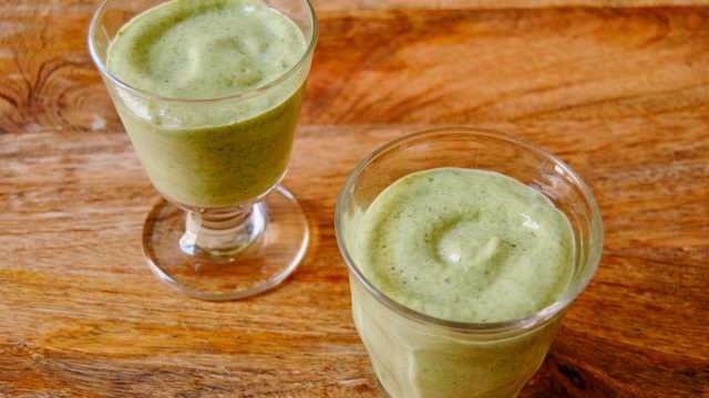 green smoothie in two glasses on wooden surface