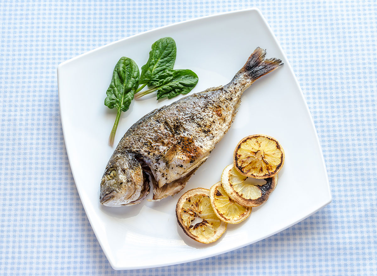 Grilled fish with lemon slices also grilled on a plate