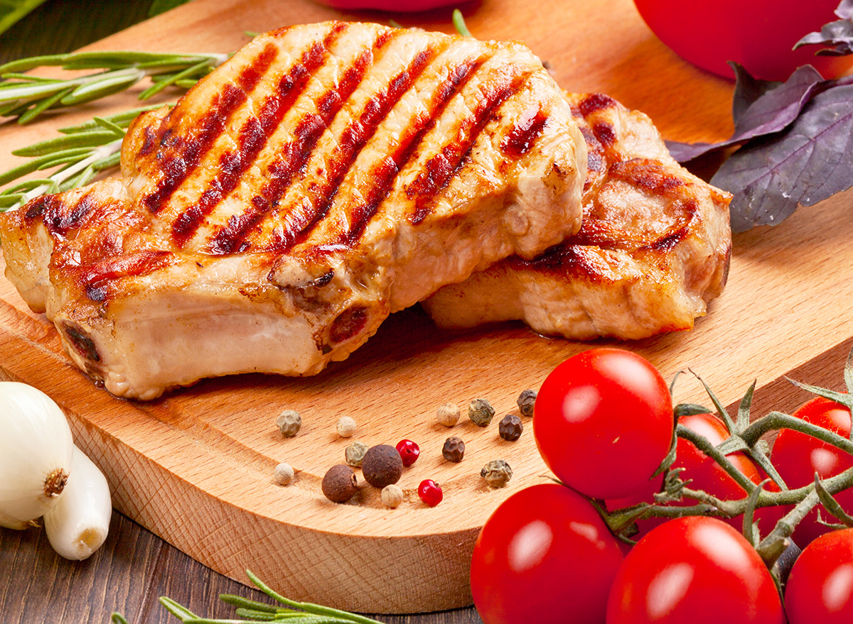 grilled pork chop on cutting board with tomatoes, garlic and peppercorn