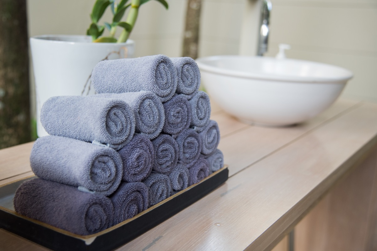 rolled towels in wooden tray at clean bathroom