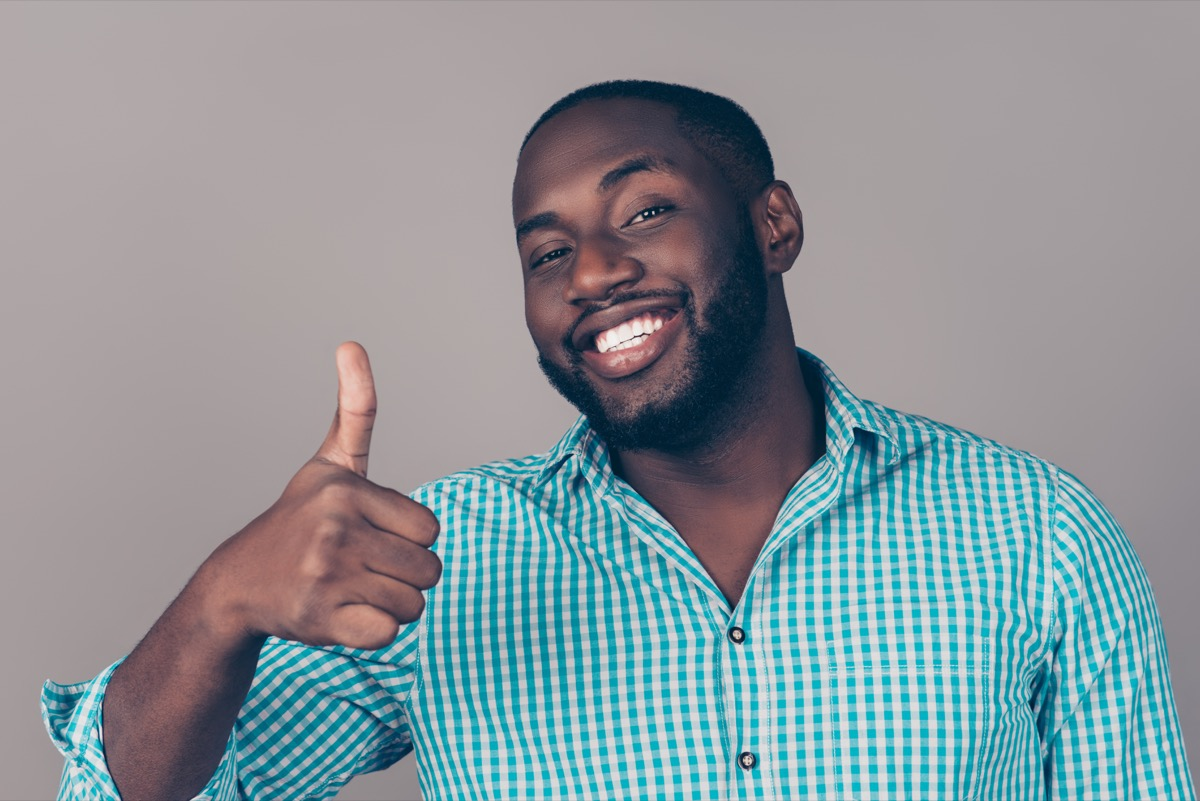 man laughing and showing thumb up gesture
