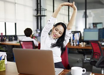businesswoman looking at work on laptop computer with satisfaction and stretching arms in the air