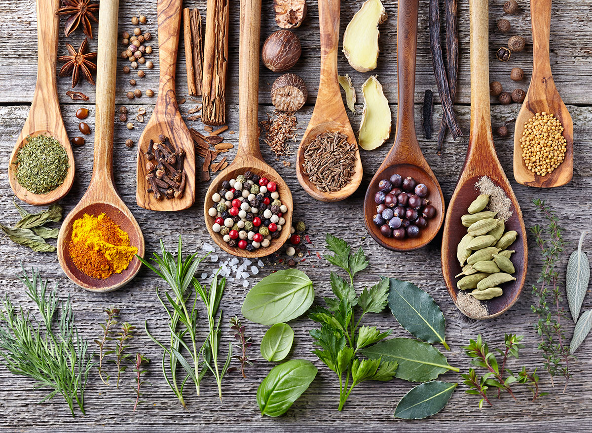 herbs and spices on wooden spoons and wooden surface