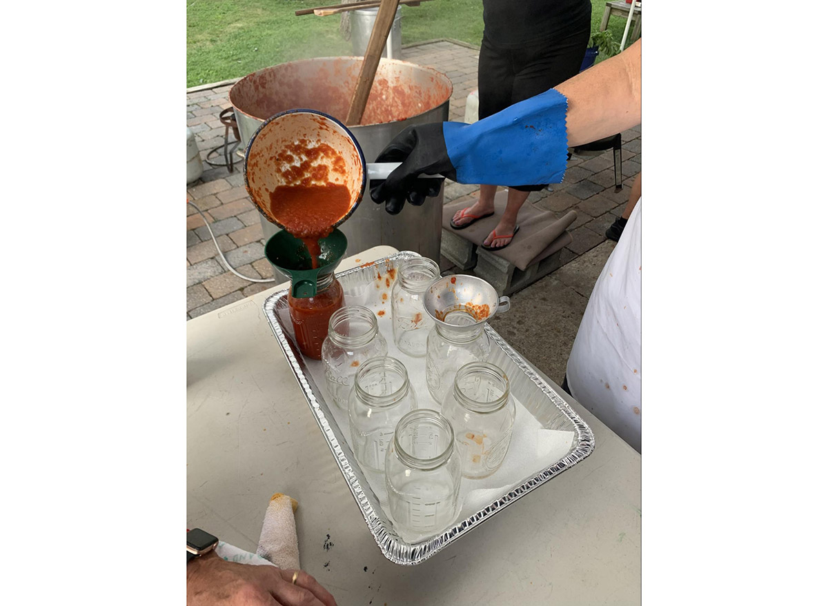 homemade sauce pouring in jars