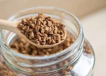 instant coffee crystals in spoon with glass jar